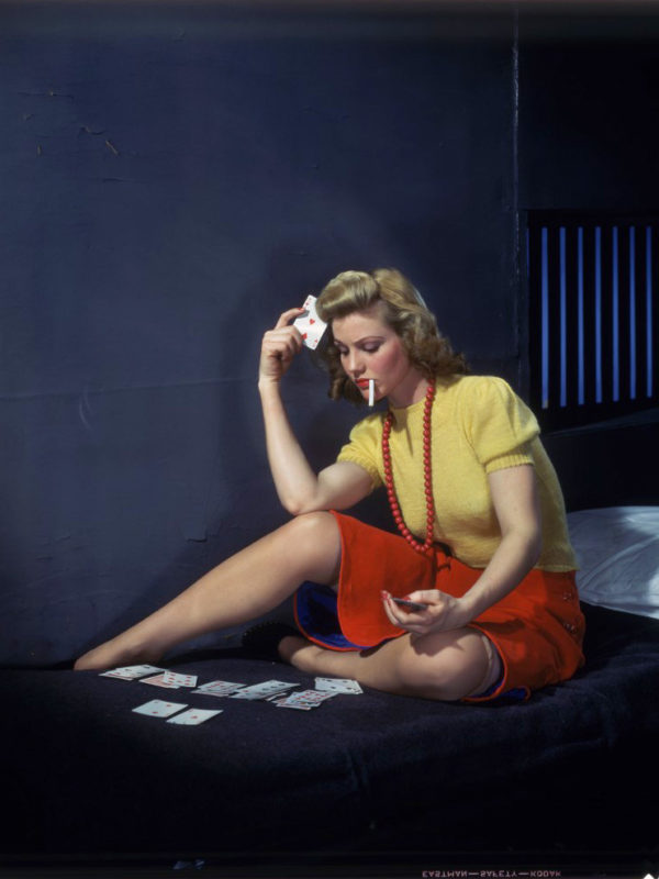 Woman in cell playing solitaire